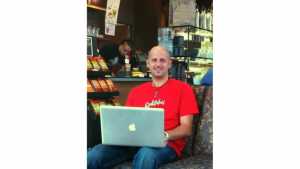 A picture of Anthony Trustee sitting in a coffee shop in his computer