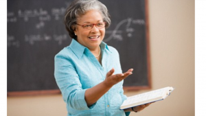A picture of an older black women talking to a class in front of a chalk board