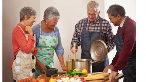 A picture of two old ladies and two old men cooking food